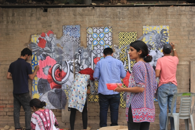The artist hard at work with her team on a graffiti.