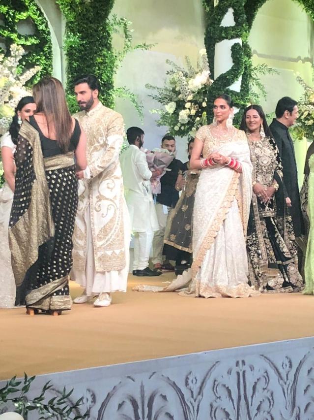 Deepika Padukone lovingly looks on as her husband 'meets & greets'.
