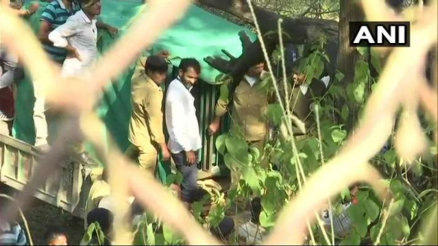 Trackers and Forest Department Personnel move the caged leopard out of the Sachivalaya.