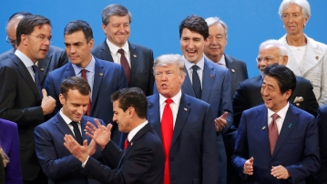 US President Donald Trump and other heads of state react to Mexico's President Enrique Pena Neto being the last one to arrive for the family photo at the G20 summit on 30 November.