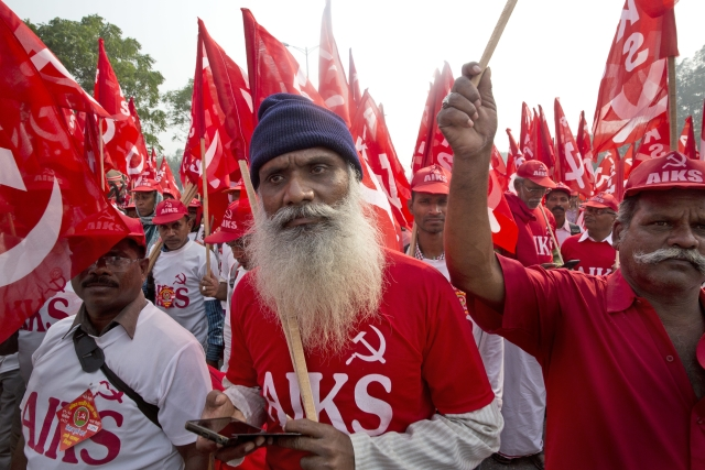 Farmers, workers and agricultural labourers wave red Communist flags as they arrive in the Indian capital for a two-day protest.