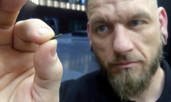 Jowan Osterlund from Biohax holds a microchip.