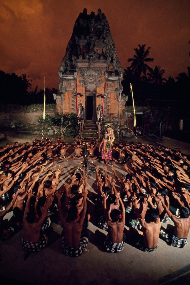 Seated villagers wave arms as they enact a play in front of a temple in Bali, Indonesia, 1969.