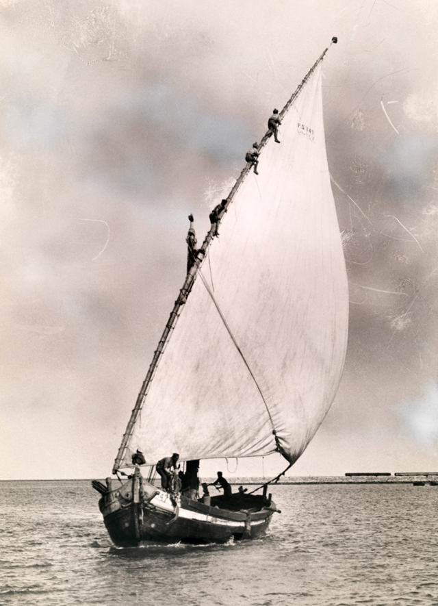 Men climb the mast of a fishing boat to furl the sail in Port Said, Egypt, 1924.