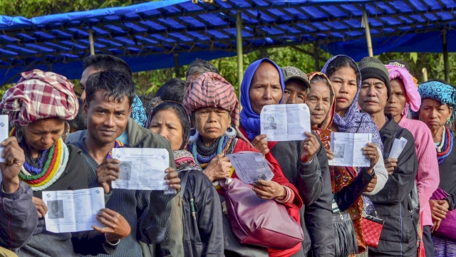Voters show their identity card as they stand in a queue at a polling station during Mizoram Assembly elections on Wednesday, 28 November.