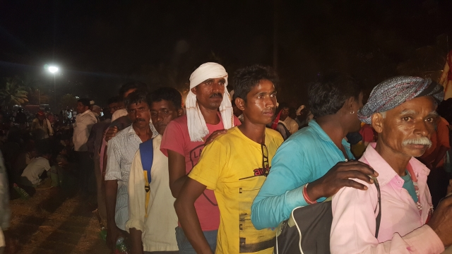 Farmers wait in a queue for dinner.