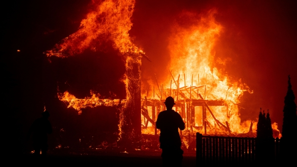 A firefighter looks on as a house gets completely burned down in the Paradise, California.