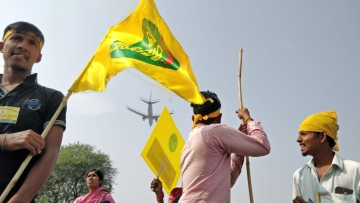 An airplane passes by as protesters take rest in Delhi's Mahipalpur, on the way to the Ramlila grounds.