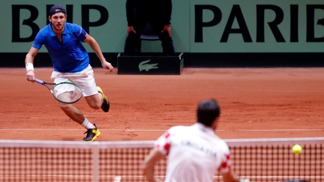 France's Lucas Pouille (left) run to return the ball from Croatia's Marin Cilic during the Davis Cup final between France and Croatia on Sunday, Novemeber 25, 2018 in Lille.