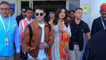 Priyanka and Nick wave to the paps as they arrive in Jodhpur.