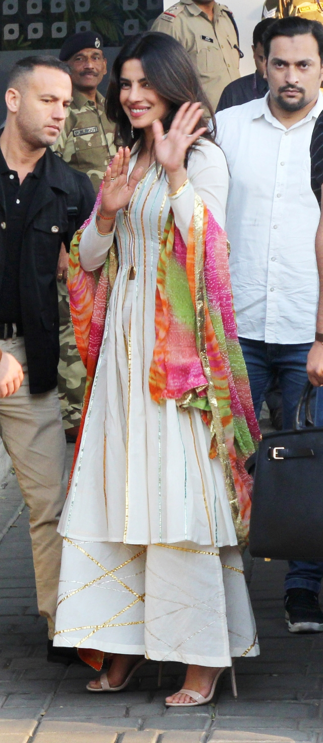 Priyanka waves to photographers as she exits into the airport.
