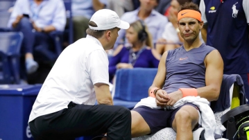 Rafael Nadal is treated by a trainer during the US Open semi-final.