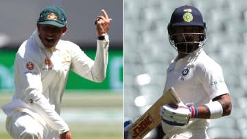 Australia's Usman Khawaja (left) celebrates after taking a catch to dismiss India's Virat Kohli (right) during the first cricket Test between Australia and India.
