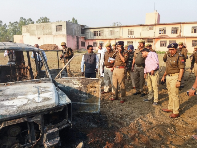 Policemen inspect after several vehicles were set on fire by a mob.