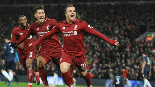 Liverpool's Xherdan Shaqiri, right, celebrates after scoring his side's third goal during the English Premier League soccer match between Liverpool and Manchester United.