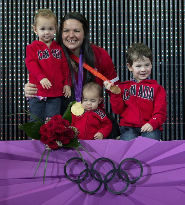 Canadian weightlifter Christine Girard poses with her children Aliana left, Samuel and Philip, right, and gold and bronze Olympic medals she was awarded during a ceremony in Ottawa.