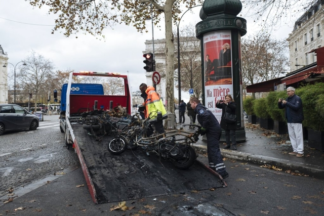 Workers clean up the street as they remove burned motorcycles, near the Arc de Triomphe in Paris.