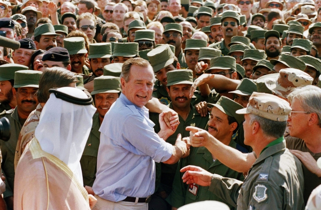In this 1990 photo, President George HW Bush is greeted by Saudi troops and others as he arrives in Dhahran, Saudi Arabia, for a Thanksgiving visit.