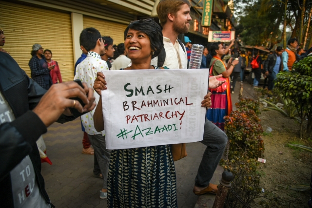 A woman flaunts a 'Smash Brahminical Partriarchy' placard at the march.