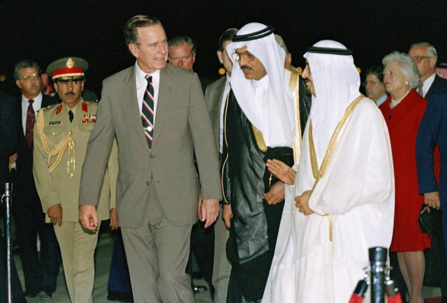 In this 1990 photo, George HW Bush is greeted by King Fahd on his arrival in Jeddah, Saudi Arabia. At right is first lady Barbara Bush.
