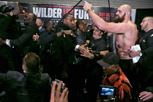 Boxers Deontay Wilder, far top left, and Tyson Fury, second from right, are separated by their respective team members after exchanging words at a news conference in Los Angeles, Wednesday, Nov. 28, 2018, ahead of their heavyweight world championship boxing match at Staples Center, on Dec. 1.