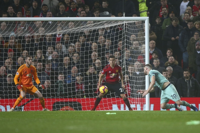 Arsenal's Shkodran Mustafi, right, heads the ball to score his side's first goal passing Manchester United's goalkeeper David de Gea.