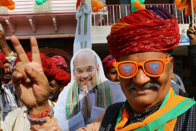 A Bharatiya Janata Party (BJP) supporter displays a victory sign in front of the cutout of BJP President Amit Shah during an election rally.