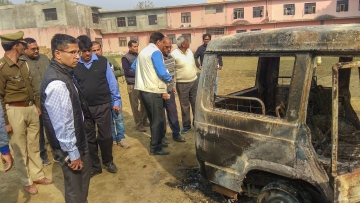 Policemen inspect vehicles set on fire by a mob on Thursday, 6 December, during a protest over the alleged illegal slaughter of cattle in Bulandshahr.