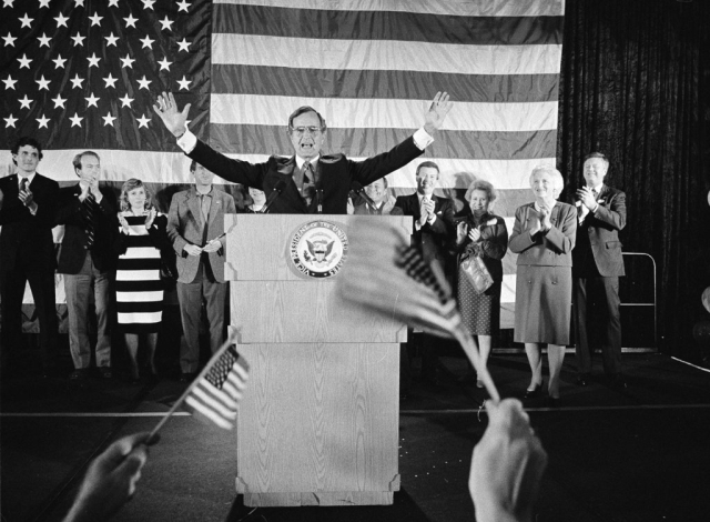 In this 1984 file photo, flag-wavers greet Vice President George Bush after he was re-elected to the post of vice president, in Houston, Texas. The vice president's wife Barbara Bush is seen second from right.