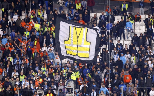 A supporter of Marseille waves a flag representing a giant yellow jacket, in solidarity with the movement of the demonstrators, called yellow jackets, who protest against the rising of the fuel taxes, during the League One soccer match between Marseille and Reims at the Velodrome stadium, in Marseille, southern France.