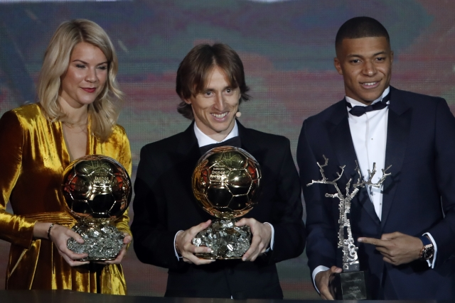 Real Madrid's Luka Modric, with the Ballon d'Or, center poses with Olympique Lyonnais' Ada Hegerberg with the Women's Ballon d'Or, left, and Paris St Germain's Kylian Mbappe with the Kopa Trophy.