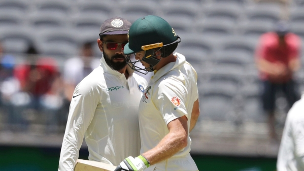 Opposing captains, India's Virat Kohli, left, and Australia's Tim Paine come face to face during play in the second cricket Test between Australia and India