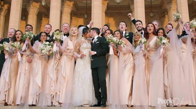The couple share a kiss surrounded by the bridal party.