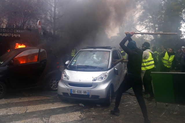 Hooded demonstrators smash a car during a demonstration on Saturday in Paris.