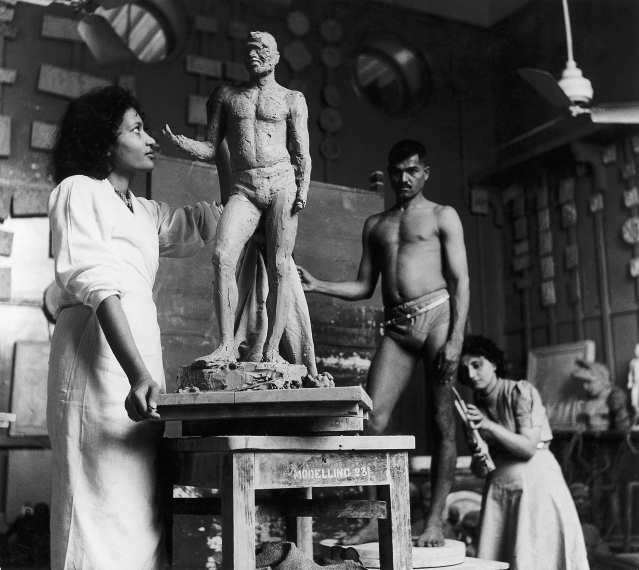 Rehana Mogul and Mani Turner at work in sculpture class at the J J School of Arts. A live male model can be seen inthe background. Bombay, late 1930s