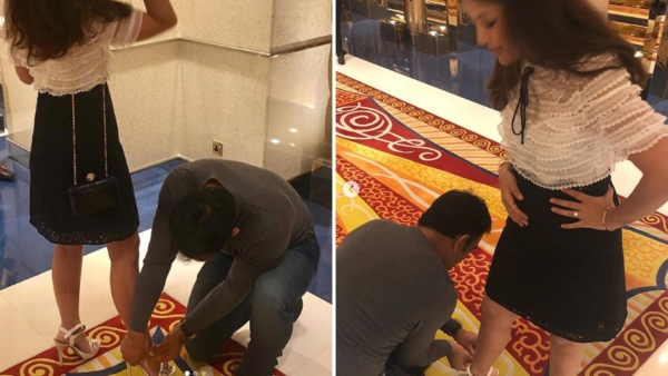 MS Dhoni ties his wife's shoe lace.