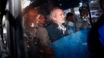 Christian James Michel (center), a British man accused of bribery in a $670 million helicopter deal between India and an Italian defense company returns after appearing before a CBI court in New Delhi.