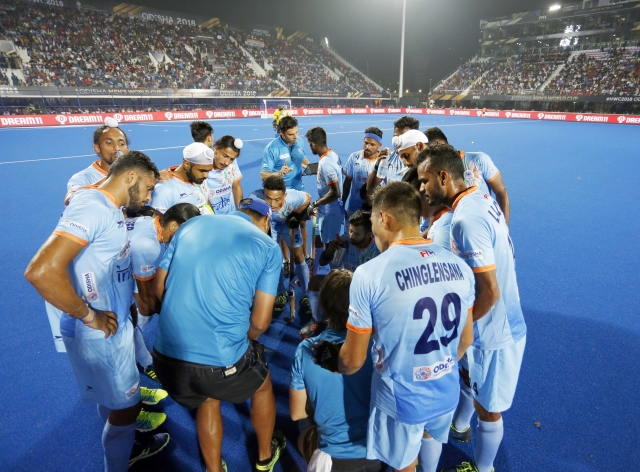 Coach Harendra Singh speaks to the Indian hockey team during half-time.