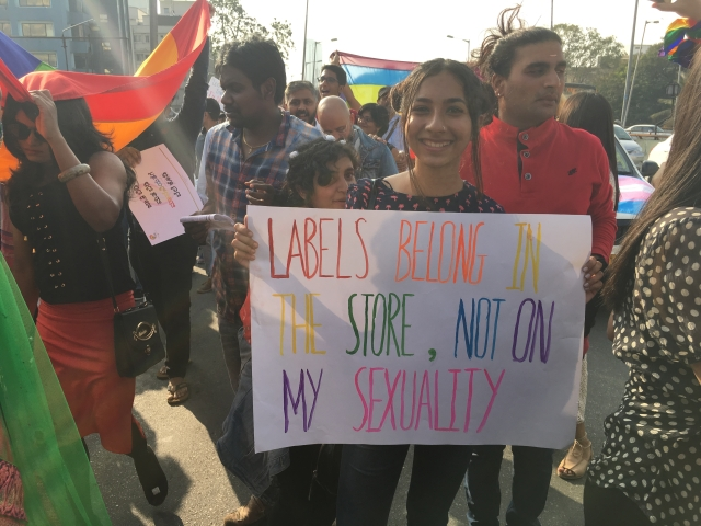 "A woman holds a placard that says, ""Labels belong in the store, not on my sexuality."""