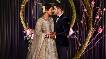 Newly-wed Bollywood actor Priyanka Chopra and American singer Nick Jonas pose for photos during their wedding reception, in New Delhi, Tuesday, Dec. 4, 2018.