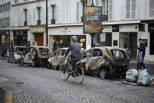 A man rides his bicycle past by charred cars near the Arc de Triomphe in Paris.