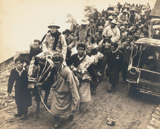 The  Dalai Lama, in ceremonial dress, enters India through a high mountain pass. He  is followed by the Panchen Lama. Sikkim, 1956