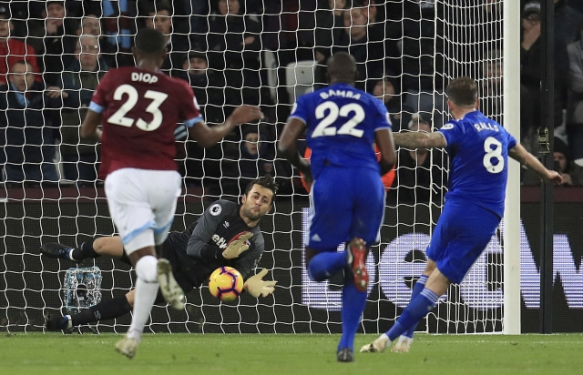 West Ham United goalkeeper Lukasz Fabianski makes a save from a penalty taken by Cardiff City's Joe Ralls, right, during their English Premier League soccer match.
