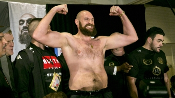 Boxer Tyson Fury flexes after exchanging words with opponent Deontay Wilder at a news conference in Los Angeles, Wednesday, Nov. 28, 2018, ahead of their heavyweight world championship boxing match at Staples Center, on Dec. 1.