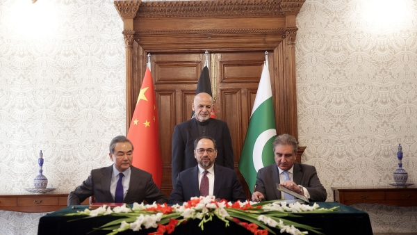 Afghanistan's President Ashraf Ghani, standing, watches as Afghanistan's Minister of Foreign Affairs Salahuddin Rabbani, center, Pakistan's Foreign Minister Shah Mehmood Qureshi, right, and Chinese Foreign Minister Wang Yi, left, sign the agreement during the meeting.