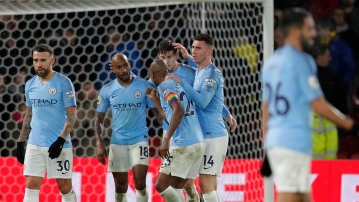 Manchester City players celebrate after winning the English Premier League soccer match between Watford and Manchester City.