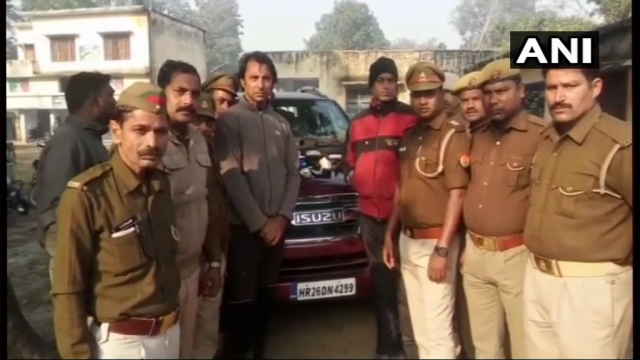 Jyoti Randhawa (center, grey jacket) pictured after his arrest on poaching charges in Uttar Pradesh's Bahraich district.