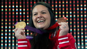 Canadian weightlifter Christine Girard holds up the gold and bronze Olympic medals she was awarded during a ceremony in Ottawa,.