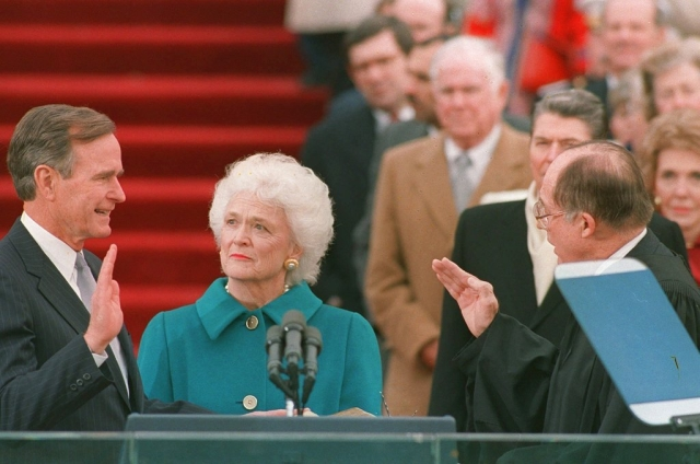 In this 1989 photo, President George HW Bush raises his right hand as he is sworn into office as the 41st president of the United States by Chief Justice William Rehnquist outside the west front of the Capitol as first lady Barbara Bush holds the bible for her husband.