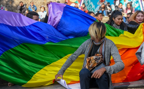 People unfurl the rainbow flag to celebrate LGBTQI+ communities.